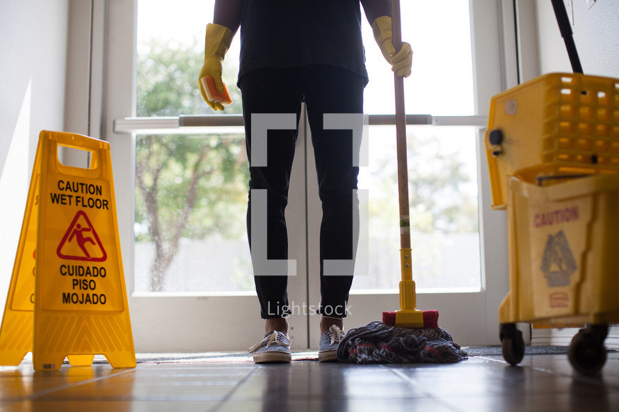 woman with a mop and wet floor sign