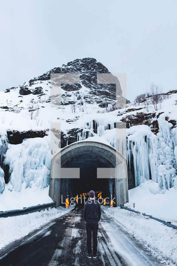 man standing in front of a mountain road tunnel in winter