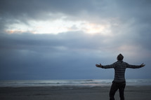 man with outstretched arms standing on a beach