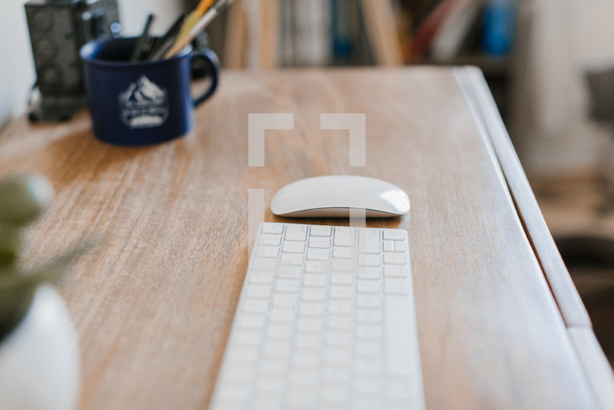 computer keyboard and mouse on a wooden desk