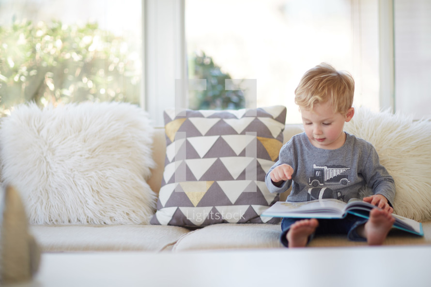 a toddler boy reading a book
