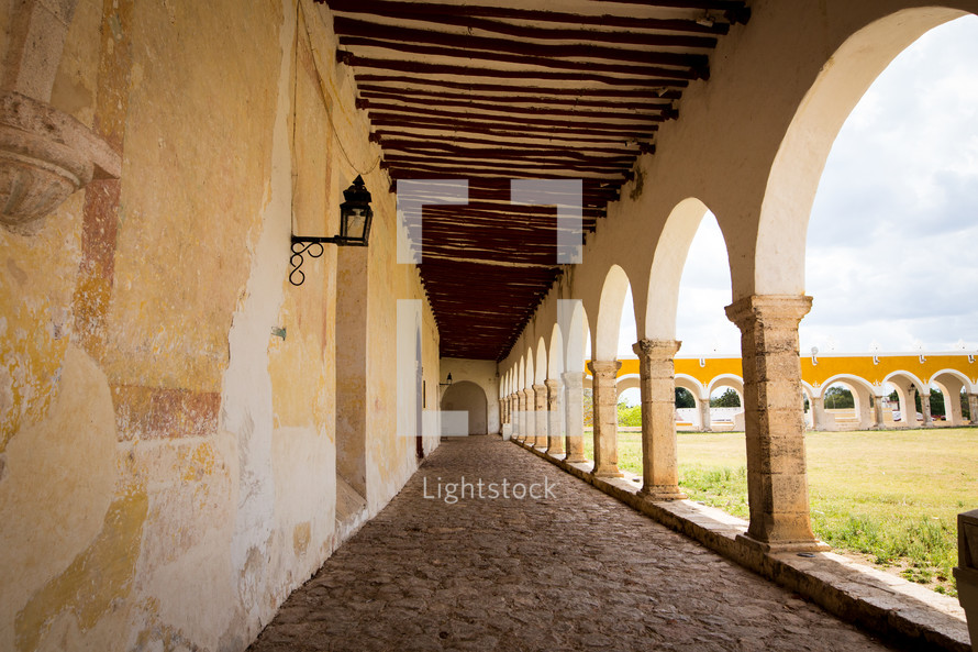 stone pavers under a covered walkway by a church