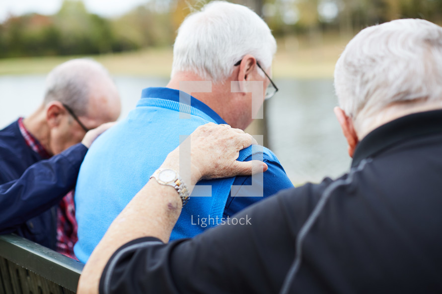 elderly men praying outdoors