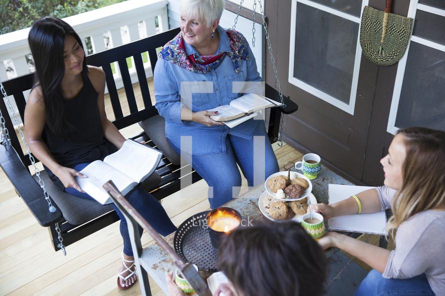 Women on a porch having a Bible study.