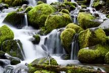 waterfalls over mossy rocks