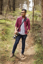 a young man with a camera standing in a forest