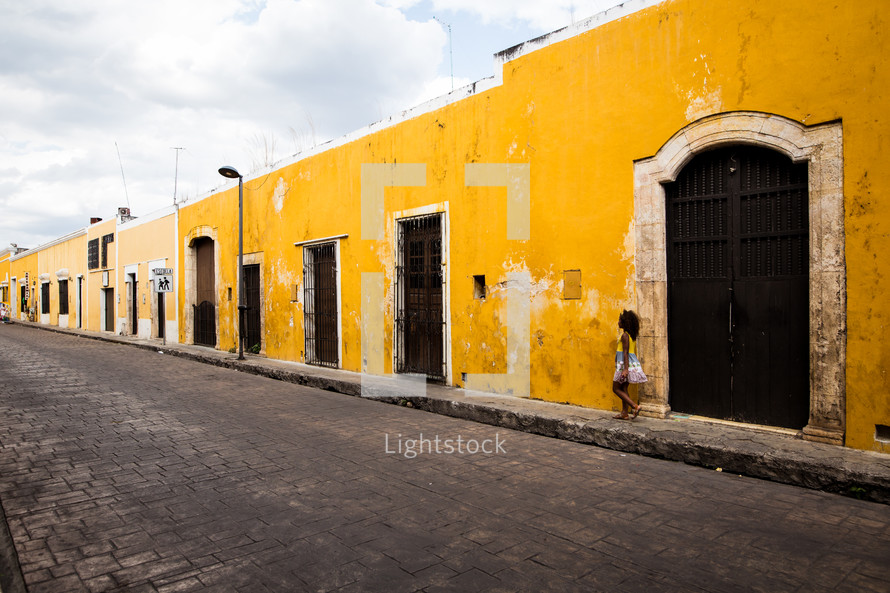girl walking on a sidewalk in front of a yellow building
