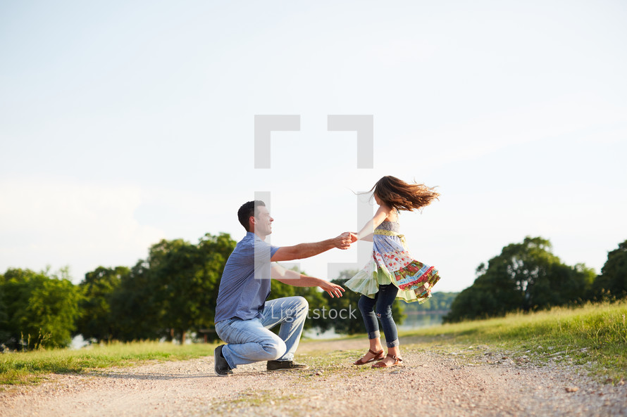 a father spinning his daughter on a dirt road