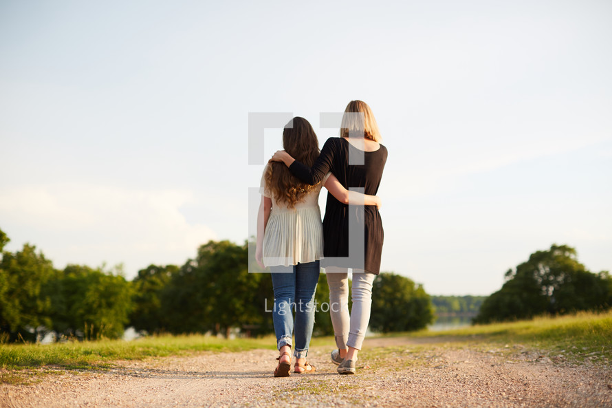 a mother with her arm around her teenage daughter