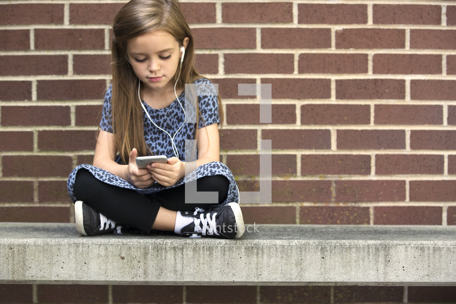 a child listening to a smart phone on a bench.