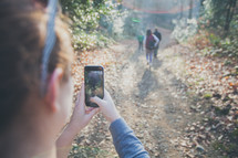 woman taking a picture with her cellphone of a group hiking on a nature trail