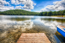 Pier on a crystal clear lake with trees and clouds on the horizon.