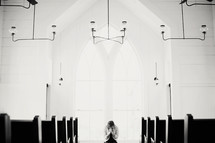 Woman praying in a church.