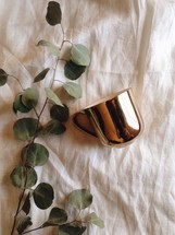leaves on a twig and metallic mug