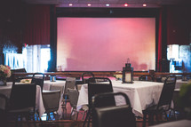 projection screen and tables and chairs set up for a wedding reception