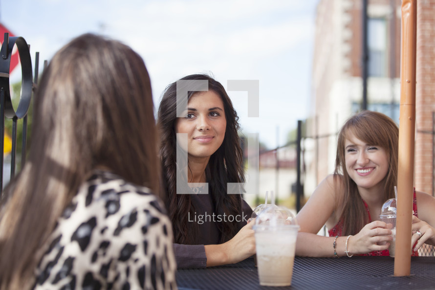 friends sitting at a table drinking milkshakes