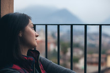 A young woman gazing out a barred window