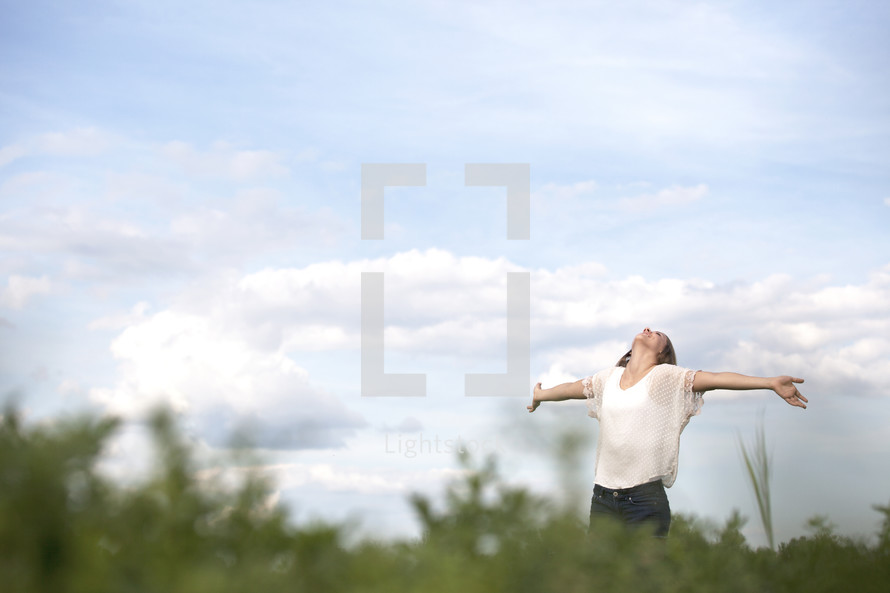 Woman standing outdoors with arms extended looking up the heavens.