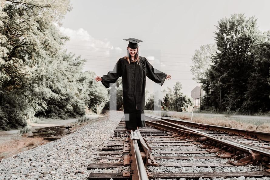 graduate balancing walking on train tracks