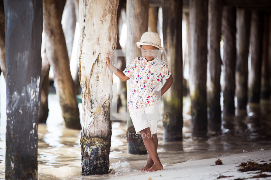 boy child standing under a pier
