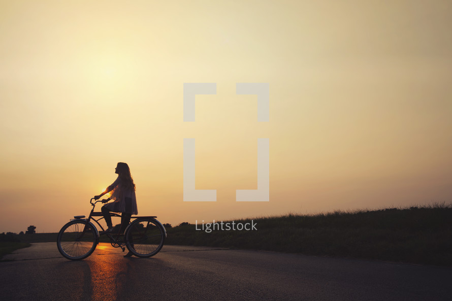 woman riding a bicycle at sunset
