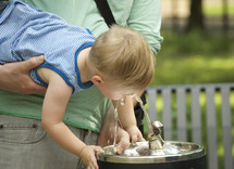 A man holding a young child up to a water fountain.