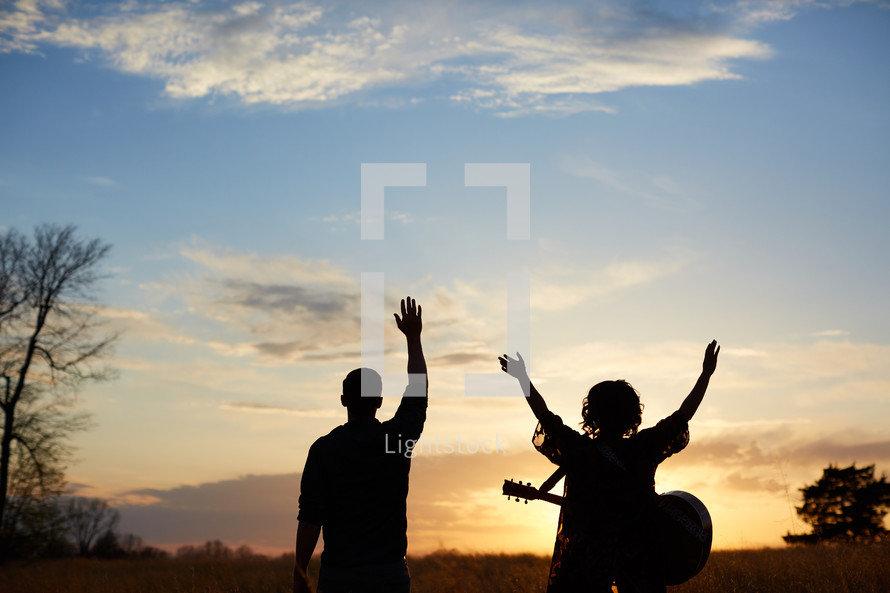 man and a woman standing in a field with a guitar at sunset