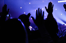 silhouettes of raised hands at a concert