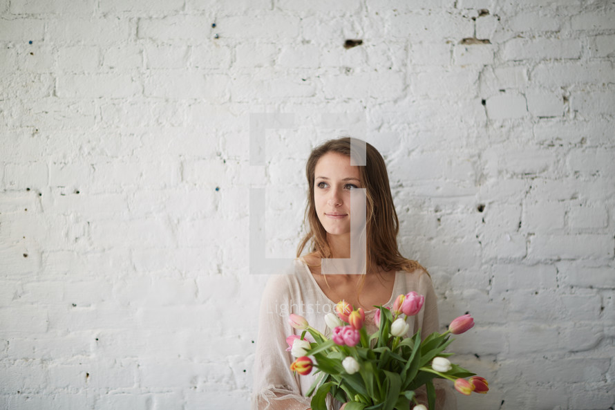 a woman holding a bouquet of tulips