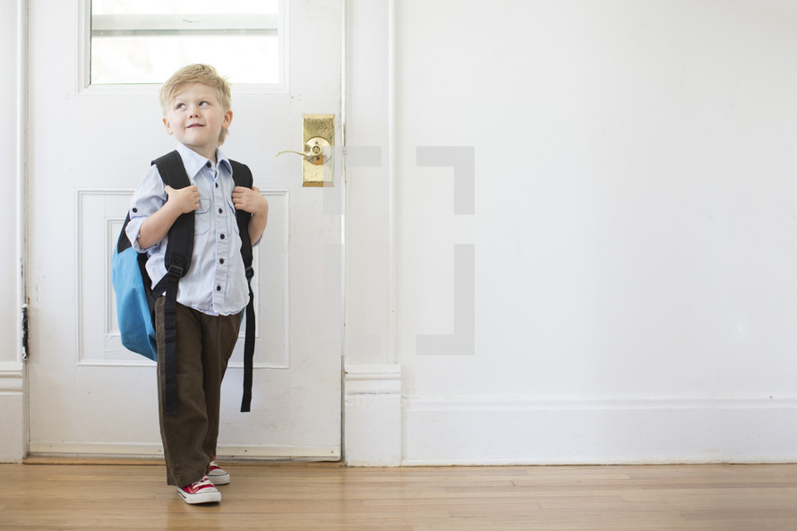 boy child with a book bag standing at a door - first day of school