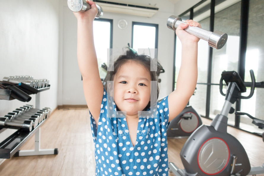 a little girl lifting weights in a gym