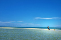 man standing on a sandbar taking pictures