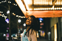 Smiling woman standing outside under a marquee of lights.