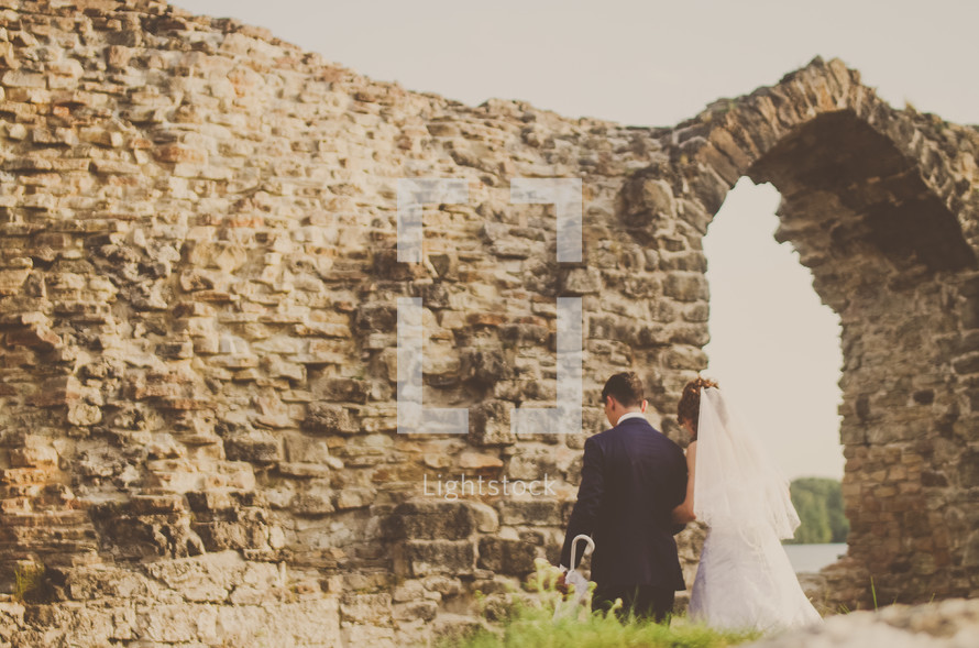 bride and groom standing in front of a stone wall