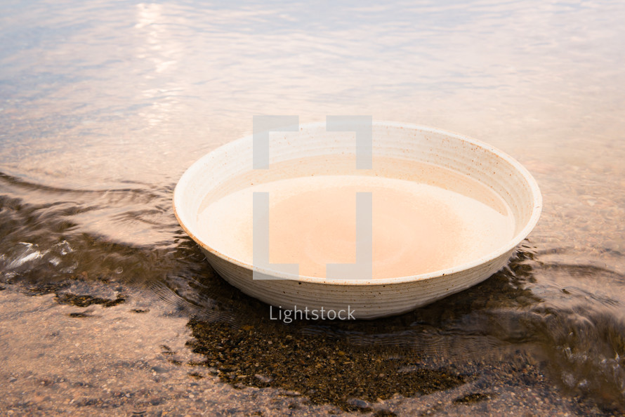 a bowl of water in the sand