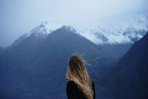 woman looking out at snowy mountains