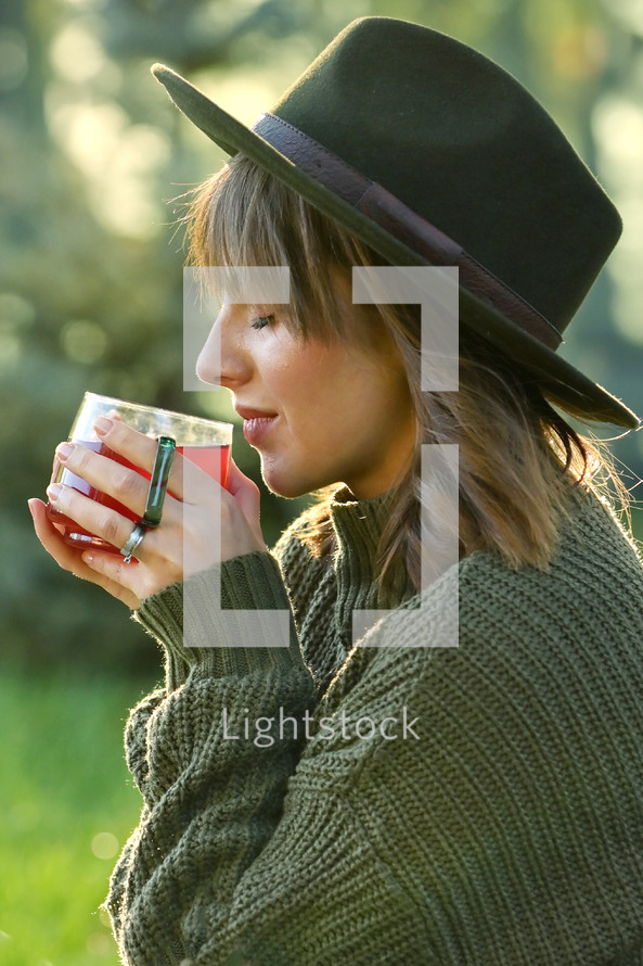 Young Woman in a hat Holding a Hot Tea Cup outdoors in fall