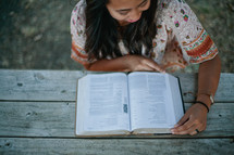 woman reading a Bible outdoors at a picnic table