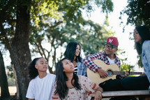 group of fiends singing and playing a guitar together outdoors