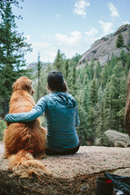 a woman sitting on a rock with her golden retriever dog