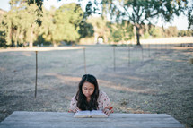 woman reading a Bible at a picnic table