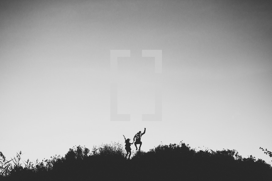 silhouette of a couple jumping holding hands