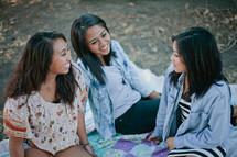 friends sitting on a blanket outdoors talking
