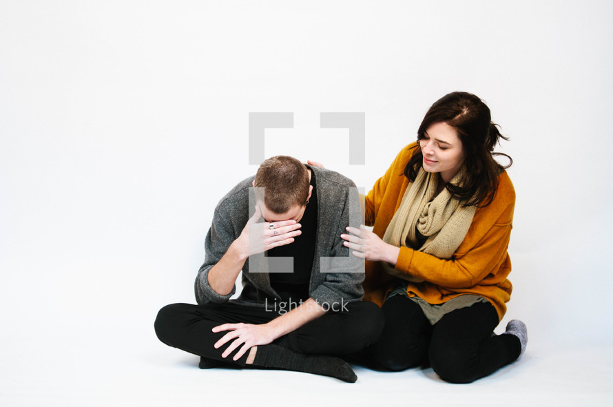a woman sitting next to and comforting a sad man