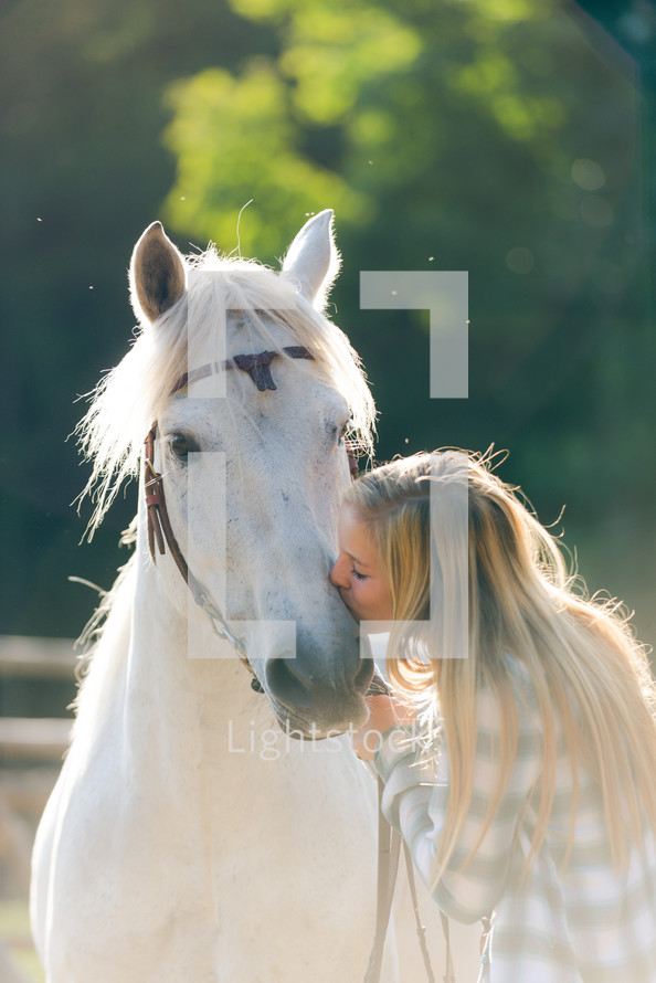 Woman kissing a horse.