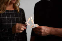 a man and woman holding a candle