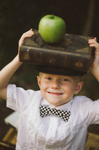 a boy child with a stack of books on his head and an apple