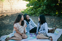 friends sitting on a blanket in the grass talking