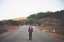 Woman standing in the middle of the road.
