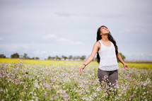 Praising woman standing in a field of flowers.
